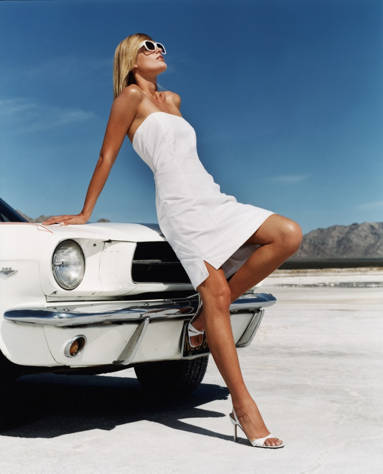5 modele de rochii albe pentru vara 2018 - femeie imbracata intr-o rochie alba care sta pe capota unei masini