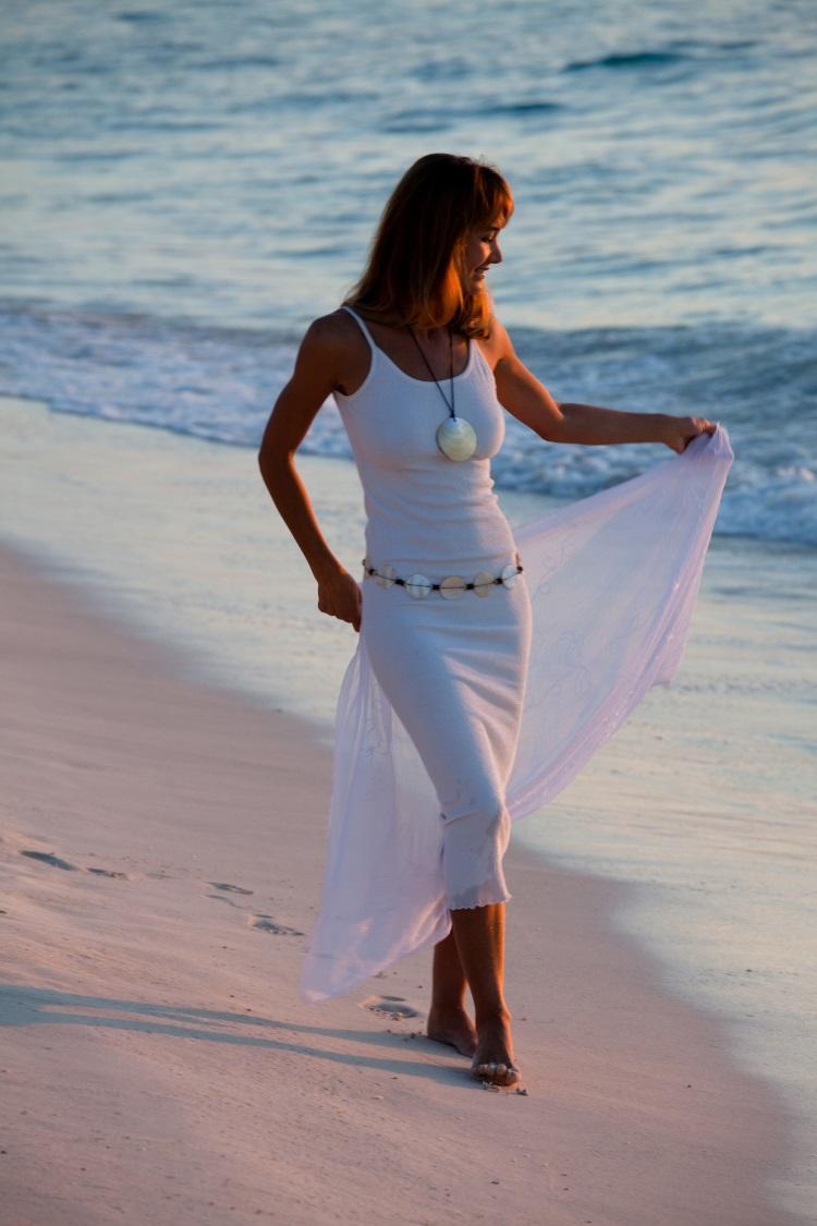 5 modele de rochii albe pentru vara 2018 - femeie in rochie alba mulata pe plaja